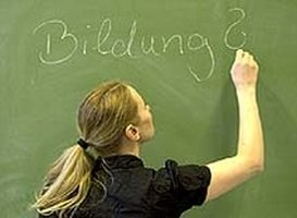 Eine Person schreibt das Wort Bildung mit Kreide an eine Tafel, mit einem Fragezeichen.